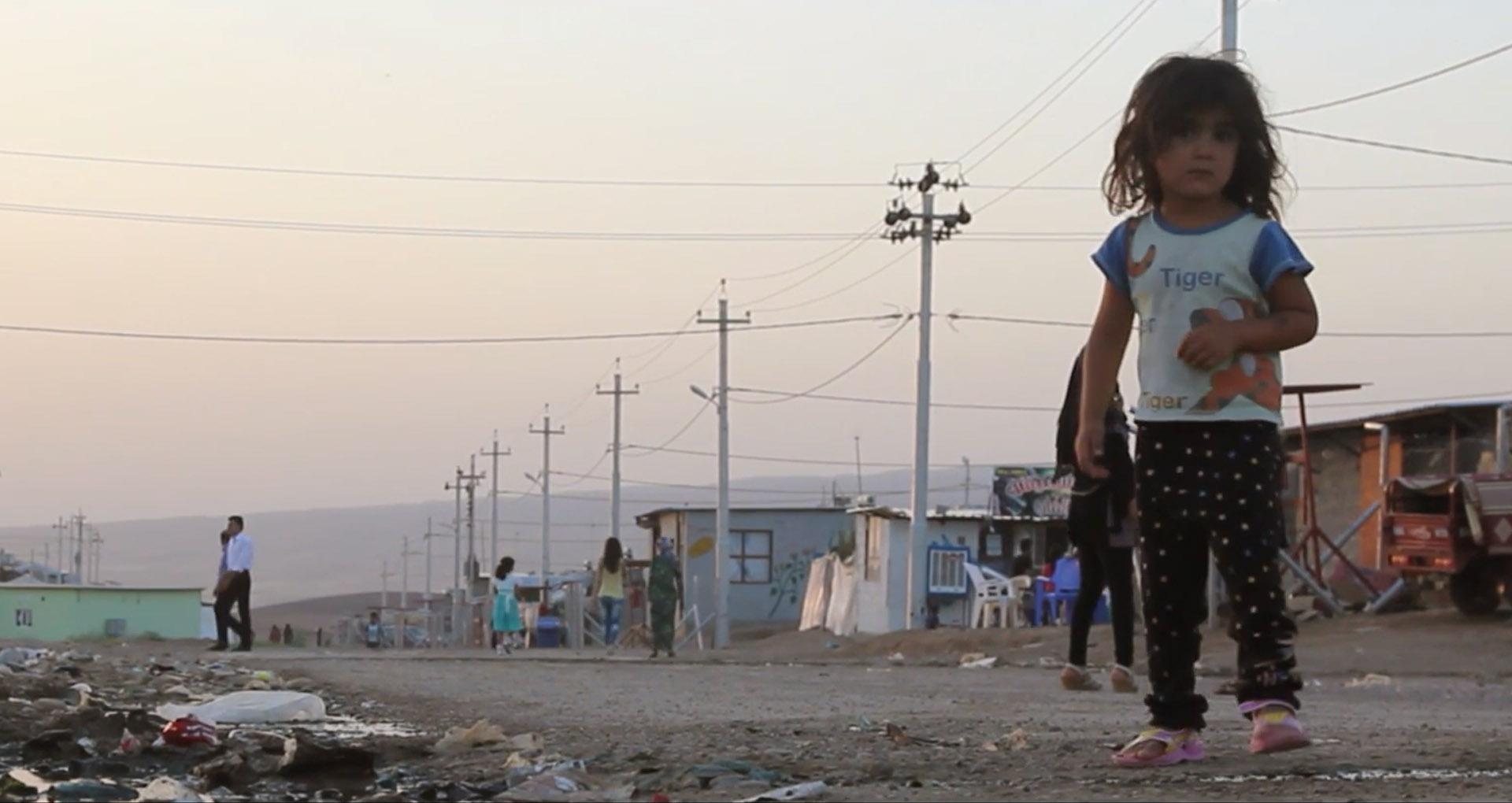 Image couleur, une petite fille en premier plan, dans un camp de réfugiés