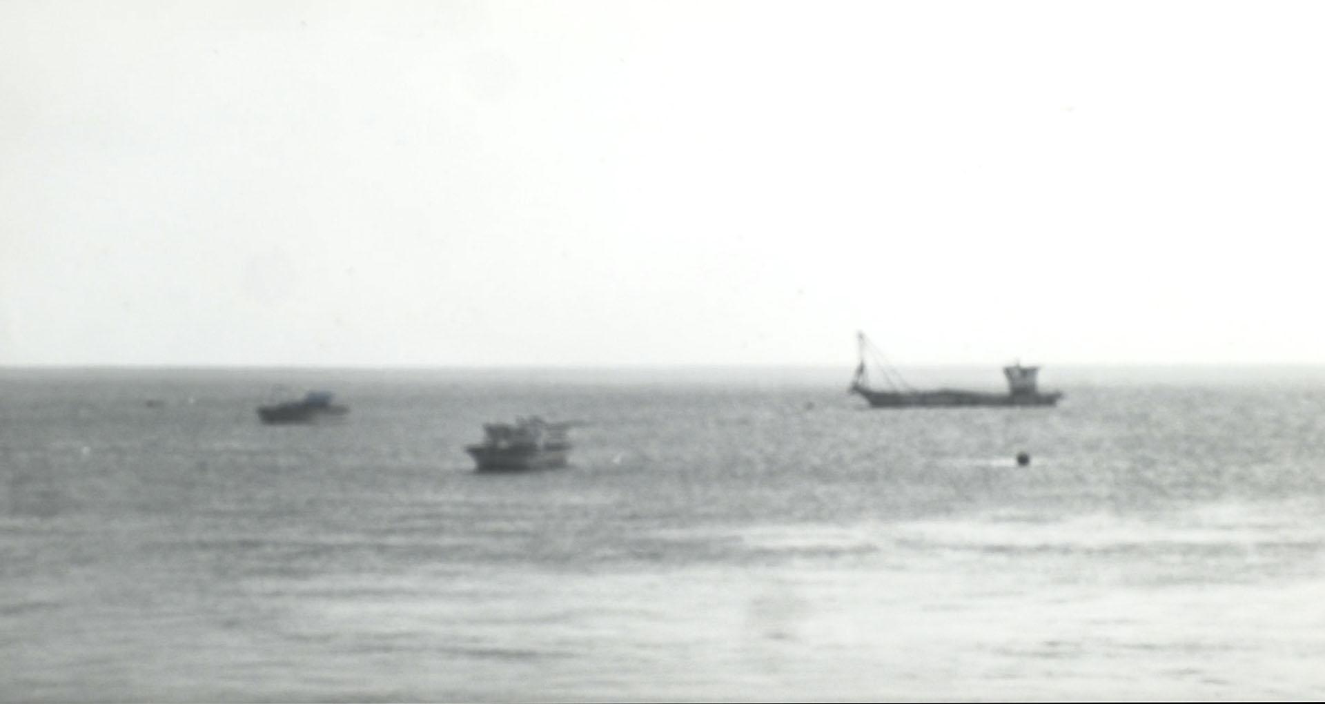 image noir et blanc, la mer et des bateaux au loin