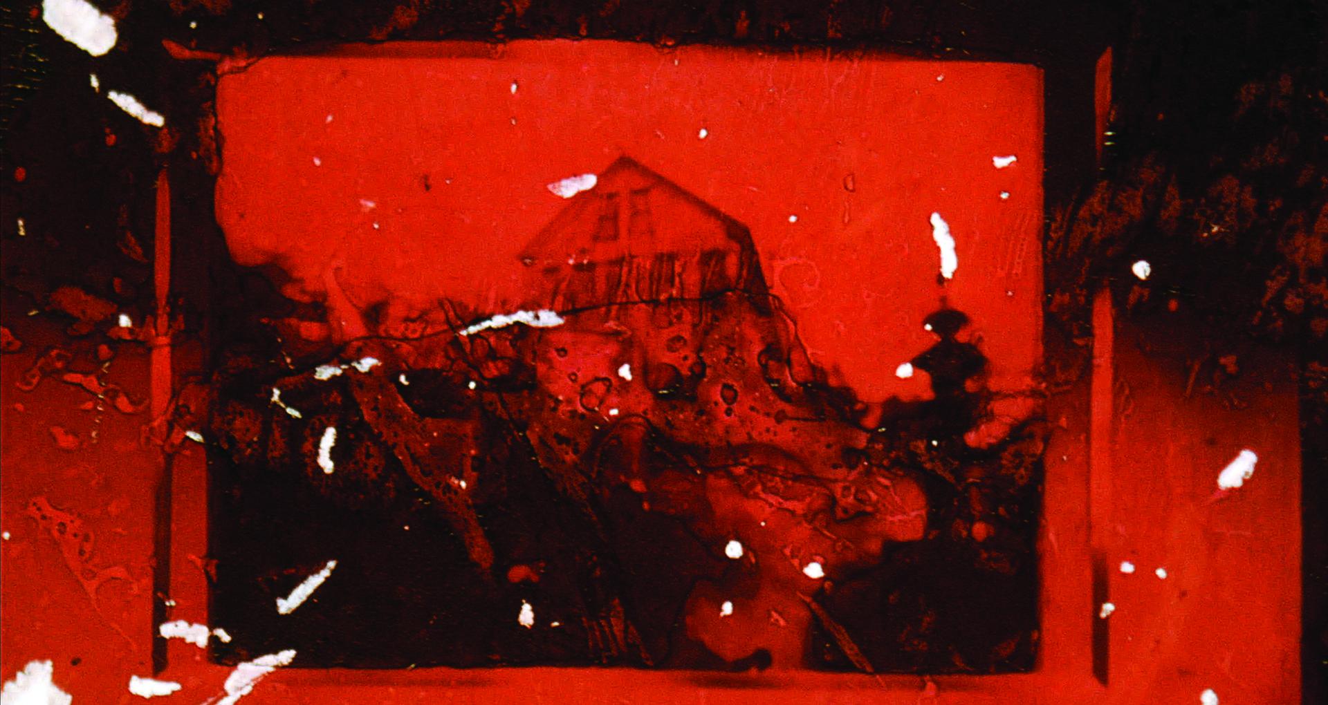 Image couleur flou, en noir et orange. Une maison en arrière plan. De la pellicule brûlée et grattée en premier plan