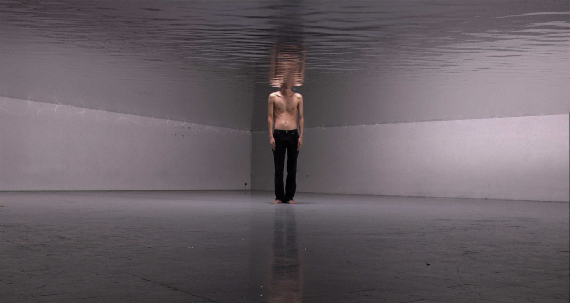 Video montage. A man standing shirtless with black pants in the middle of a room. The upper half of the room is immersed in the water and the character's head too.