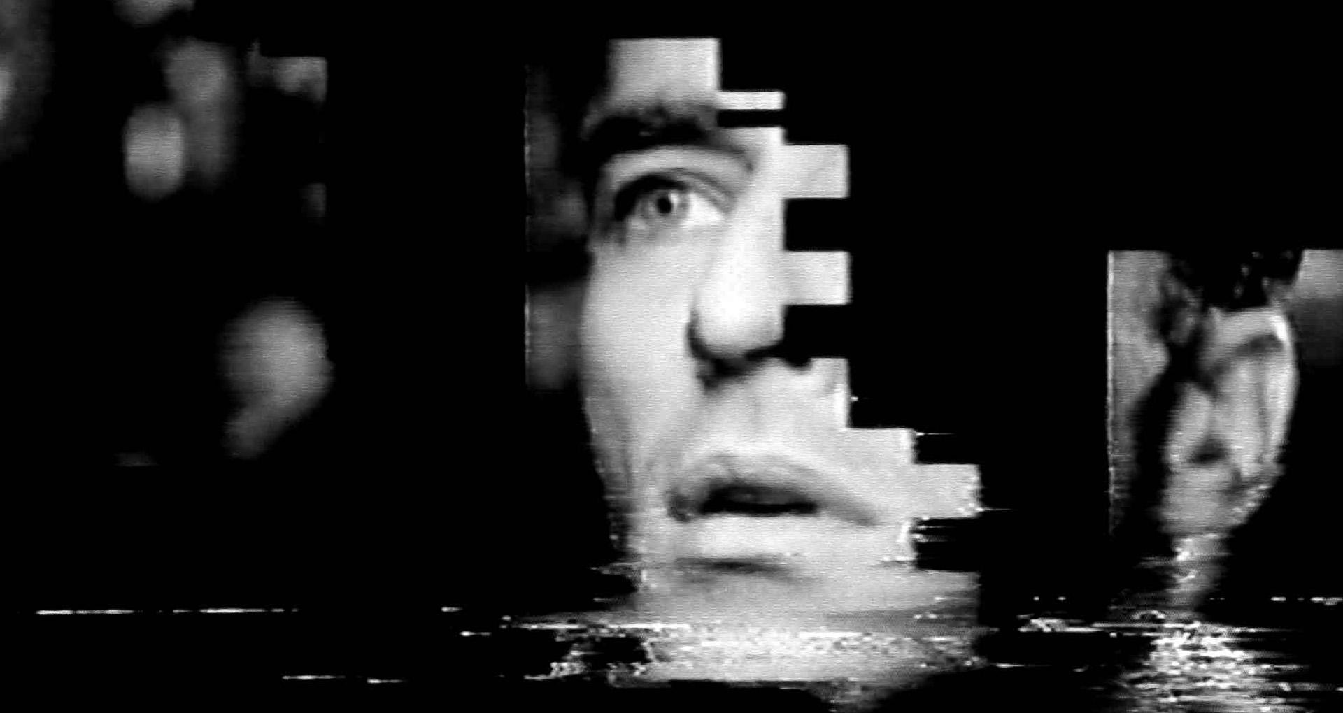 Image vidéo en noir et blanc. Le visage d'un homme est découpée en morceau