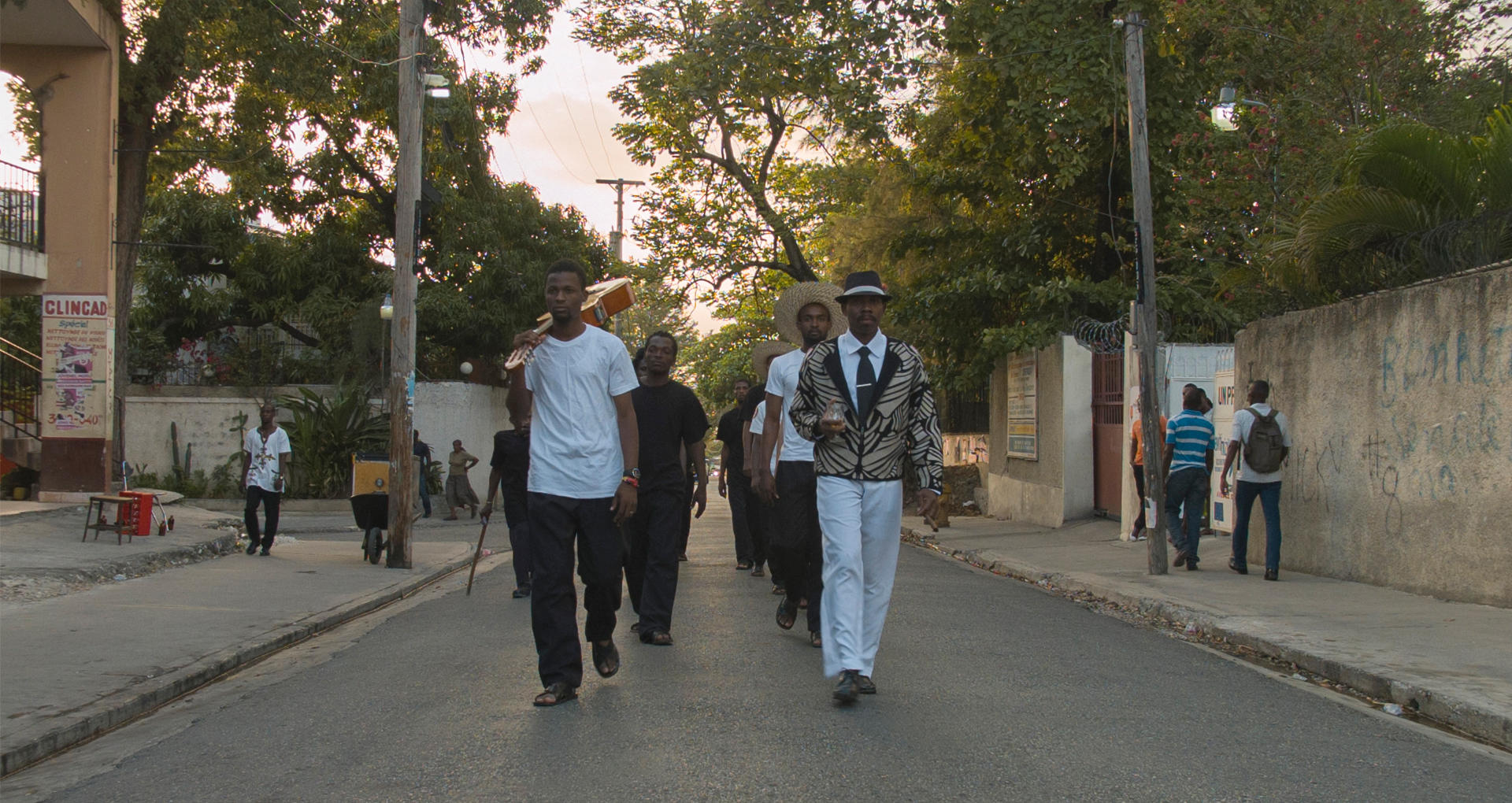 A group of men dressed in black and white walk in the middle of a street in Port au Prince.