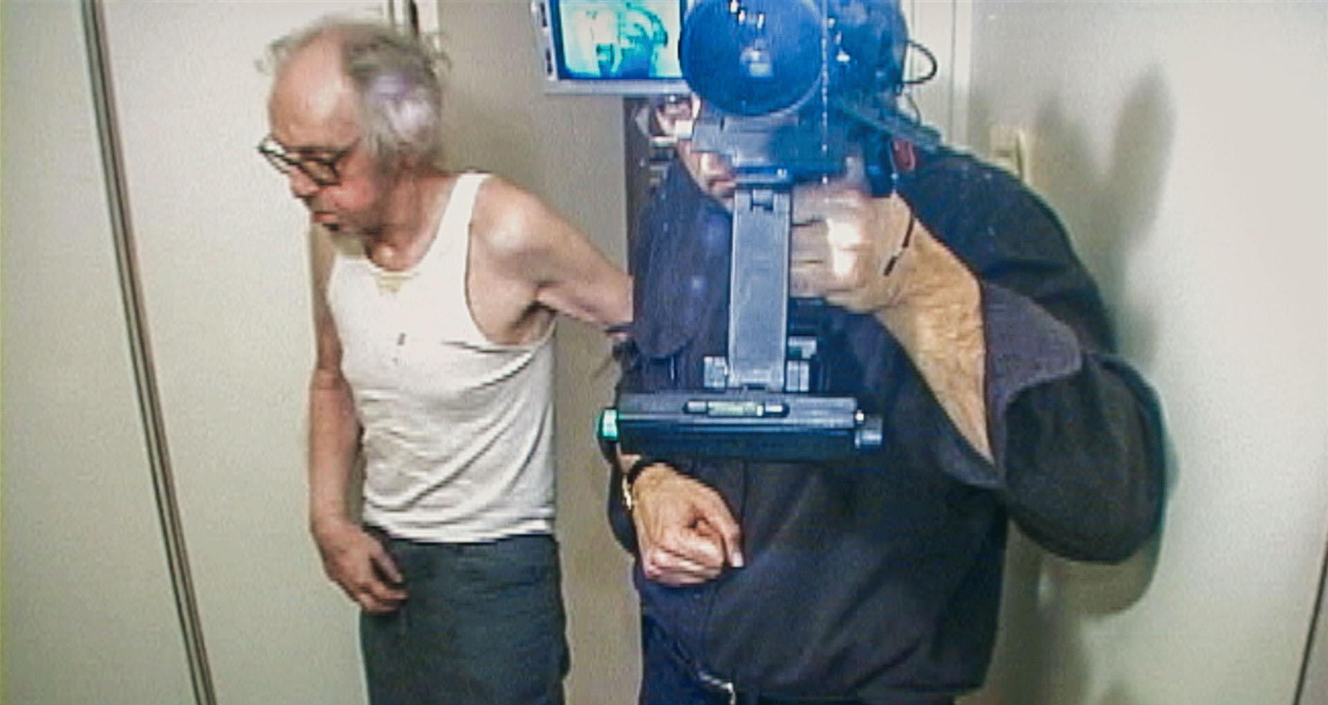 deux hommes devant un miroir, l'un a une caméra