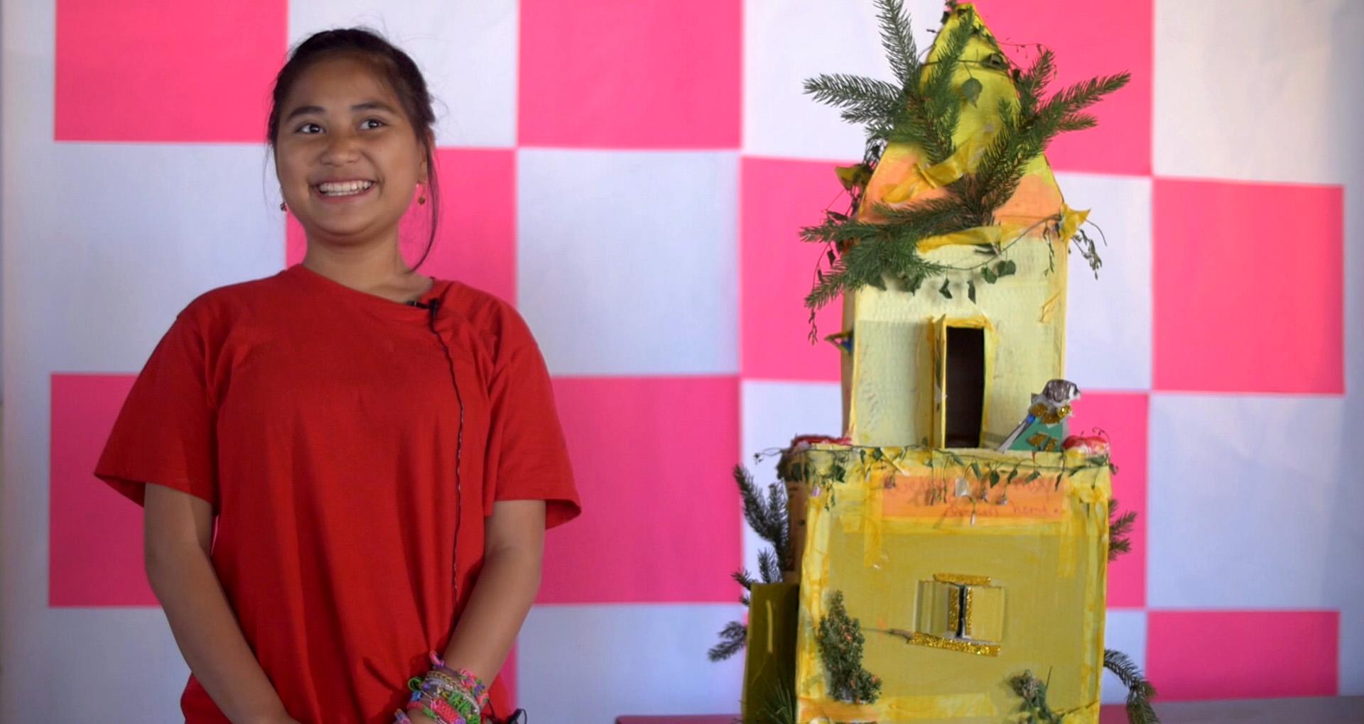 petite fille en tshirt rouge su fond rose et blanc à damiers, devant un château en carton peint en jaune